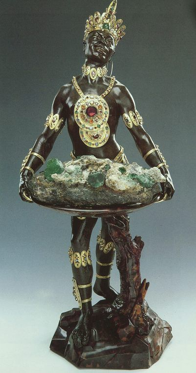 """Ceremoniele Moor, 1724,  One of the finest examples of a blackamoor in the arts is the Mohr mit Smaragdstufe (""""Moor with Emerald Cluster""""), in the collection of the Grünes Gewölbe in Dresden, Germany. It was created by Balthasar Permoser in 1724. The statue is richly decorated with jewels and is 63.8 cm (2.09 ft) high."""