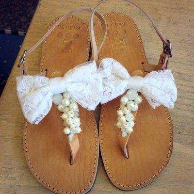 Δερμάτινες χειροποίητες σαγιονάρες με ένα φιόγκο από άσπρη κορδέλα και άσπρες πέρλες.