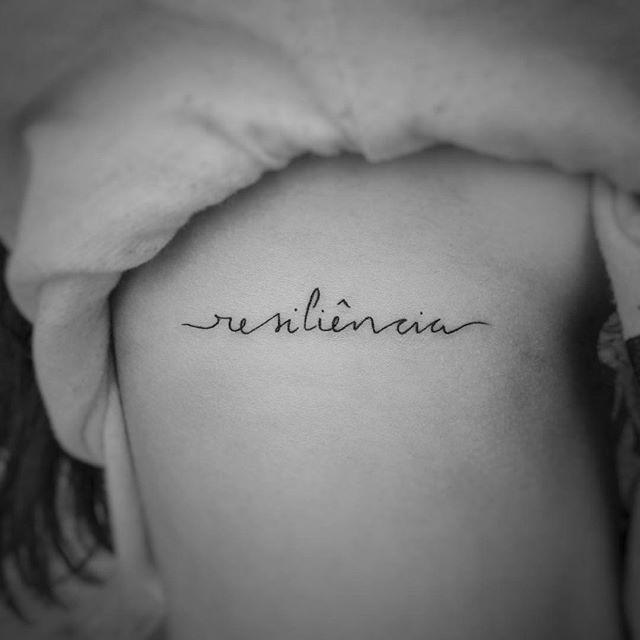 """Nós percebemos que não temos postado tantas fotos de escrita, vocês acham que a gente deve postar mais fotos assim? Responda nos comentários.  Essa escrita linda foi feita pela artista baiana <a href=""""http://instagram.com/rekabittencourt"""">@rekabittencourt</a>, que temos a honra de acompanhar desde o início do <a href=""""http://instagram.com/tattoo2me."""">@tattoo2me.</a>  Resiliência: Capacidade de se recobrar facilmente ou se adaptar à má sorte ou às mudanças."""