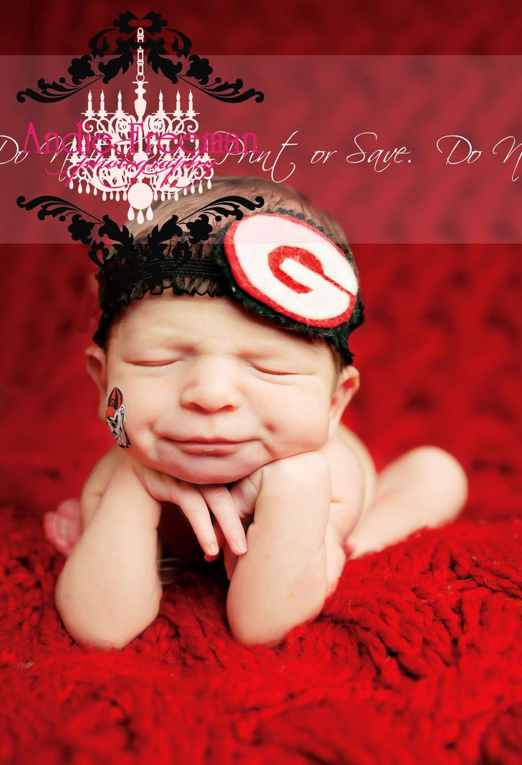 Newborn baby girl on red blanket with Georgia Bulldogs football headband. www.TheAthensNewbornPhotographer.com