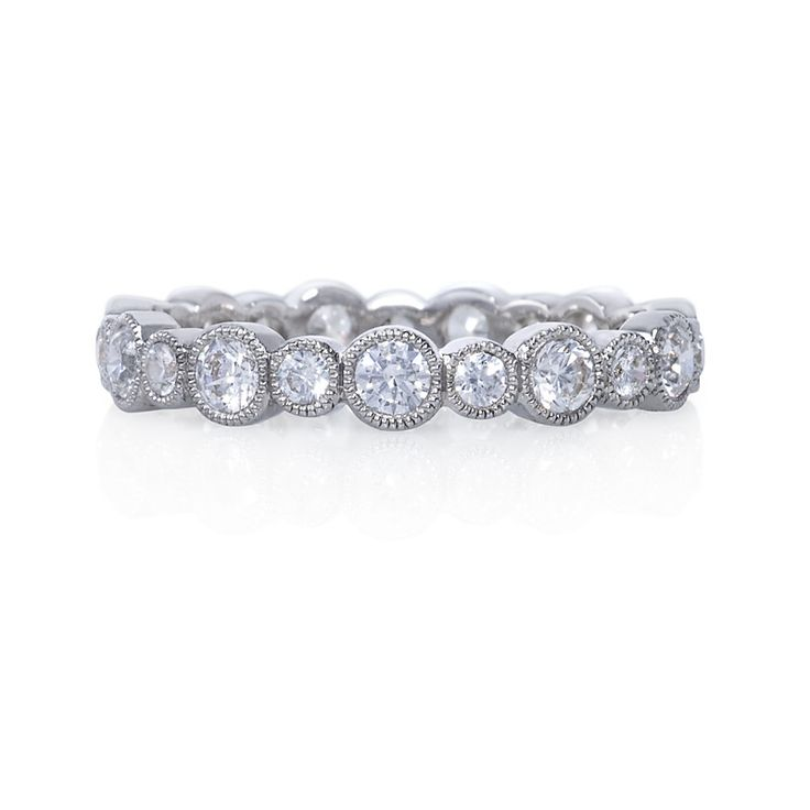 Alternating sizes of round, brilliant diamonds are wrapped in fine milgrain in this whimsical women's wedding band, which is the perfect accent to multiple engagement rings.