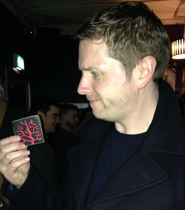 A Cage of Roots author Matt Griffin examines the artwork on a cookie of the book(ie)