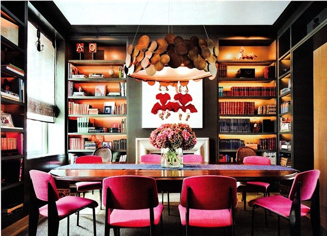 The warm Hermes orange bookshelves are given a special magical quality with the recessed lighting ... The HOT pink of the chairs plays beautifully against the orange and the natural wood chandelier gives the space a grounded magical feeling.