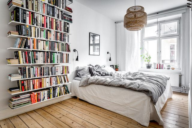 Grey linen bedding and lots of books in a Swedish bedroom.