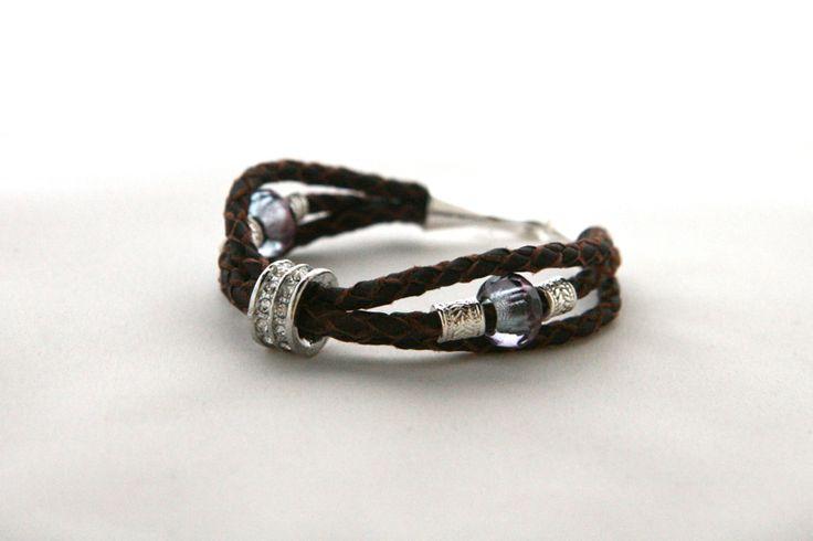 Armband med flätor av mörkbrunt renskinn, glaspärlor och silverfärgad metall