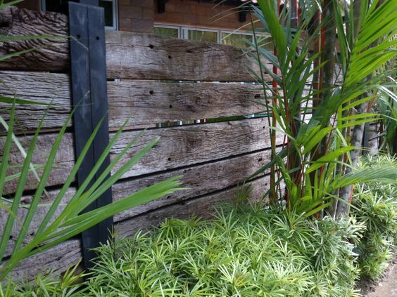 Railway sleeper fence - perfect for the back laneway, maybe the neighbours' side, too. Use some U-shaped purlin as uprights.: