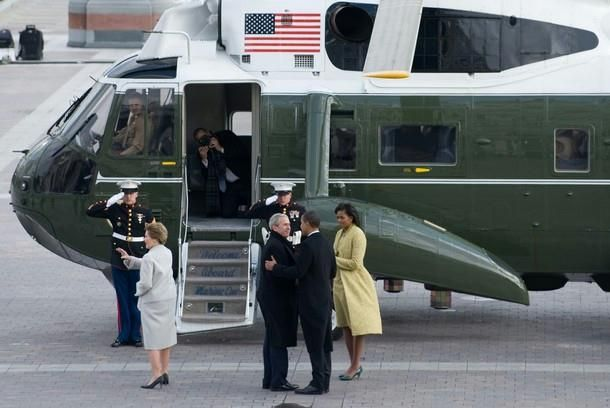 US President Barack Obama talks with former US President George W. Bush with First Lady Michelle Obama and Laura Bush as the Bush's prepare to leave the US Capitol on the presidential helicopter after Obama was sworn in as the 44th US president in Washington, DC, on January 20, 2009.  [Two anti-missile countermeasure devices at right of Michelle.]