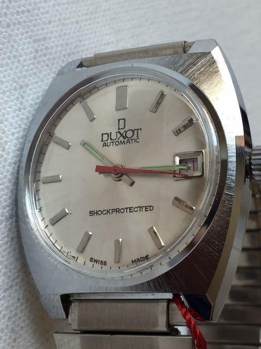 Duxot - automatische - mannen - 1970th-Zwitserse  Maken: DuxotModel: ZwitserlandKaliber: 5203Juwelen: 17 / handmatige wind.ShockprotectedOnbreekbaar voorjaarCase size: 38 mm zonder kroonZaak grootte van lugs tot lugs: 41 mmVoor elke omvang flexibele band: armband. Dit horloge heeft het enigszins ongebruikelijke vlakke voorpaneel ontwerp waardoor het horloge onderscheidt van veel van de jaren 70 ontwerpen en het ziet er heel slim. Het zelfs 007 referentie maar ik weet niet of het een…