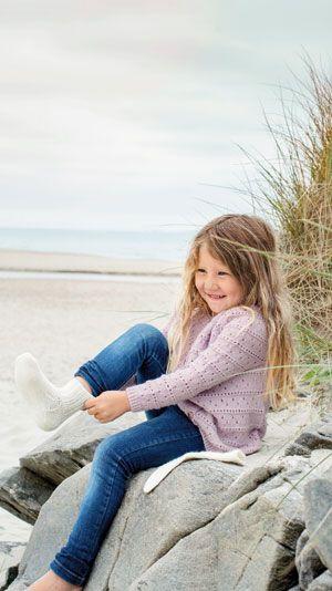 Strikkeopskrift: Et sødt lunt sæt til lillepigen bestående af en rosa cardigan og tykke hvide sokker. Cardiganen har mange fine detaljer bl.a. et lille hulmønster og en snoet kant ved kraven. En rigtig prinsesse bluse.