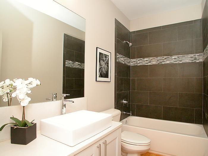 this modern bathroom features a tile tub surround with glass tile accents and a floating vanity