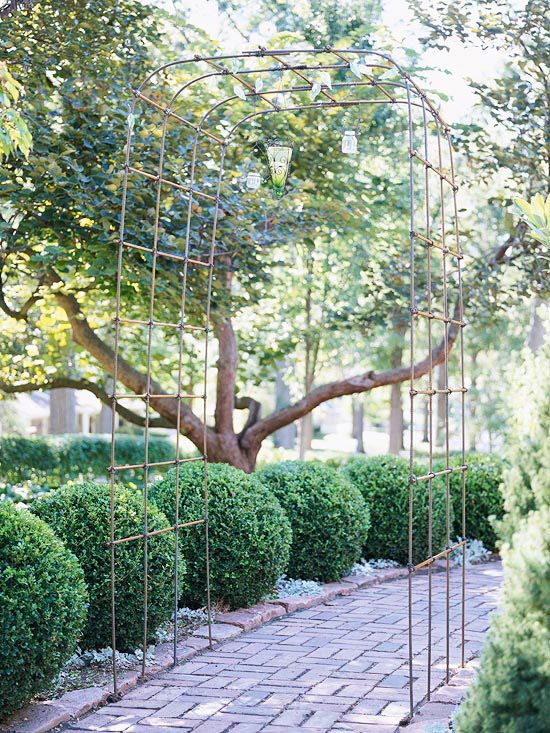 Simple and Graceful Metal Arbor. Candles suspended, hanging lights - appealing both day and night. Frames path...