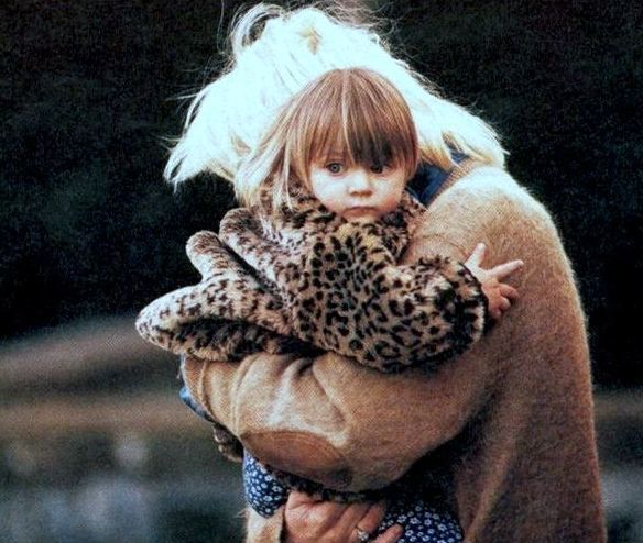 Courtney Love on the day of husband Kurt Cobain's funeral, wearing one of his sweaters and holding their 18 month-old daughter Frances Bean