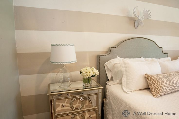 Adorable boy's nursery guest room features white moose head on striped walls framing studded gray headboard accented with soft white bedding next to clear glass lamp with white and blue lamp shade on mirrored nightstand.