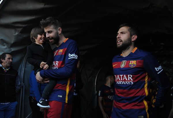 Gerard Pique and Jordi Alba of FC Barcelona celebrate after beating Granada CF 3-0 to clinch the La Liga title during the La Liga match between Granada CF and FC Barcelona at Estadio Nuevo Los Carmenes on May 14, 2016 in Granada, Spain.