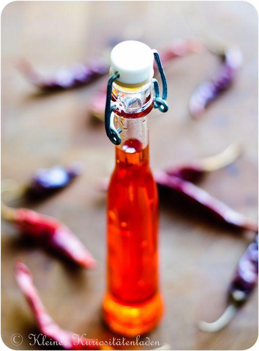 Chili-Öl 150 ml Erdnussöl  50 ml helles Sesamöl  40 g getrocknete Chiliflocken  3 Cascabel-Schoten, zerbröselt oder eine Ancho-Chili  Zubereitung  Das Öl in einen Topf geben und erhitzen Die Chiliflocken dazugeben, as Öl soweit erhitzen, dass die Flocken einmal aufschäumen und dann von der Platte ziehen. Abgedeckt über Nacht ziehen lassen.  Durch ein Sieb filtern und in einer Flasche im Kühlschrank aufbewahren.