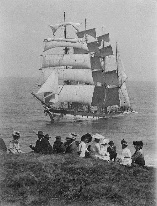 This must have been quite a harrowing scene.. This beautiful ship is at her end and sinking.. The spectators seem more in awe at the arrival of a camera... Do you think perhaps they were passengers??
