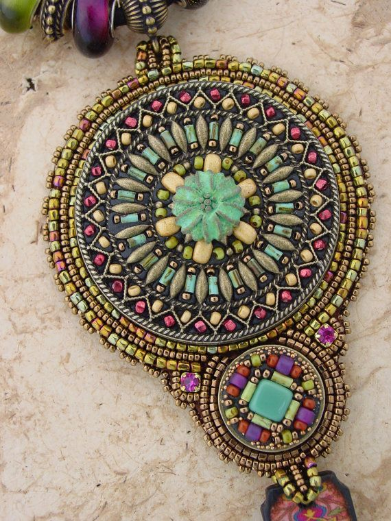 This beautiful necklace has an amazing filigree top filled with colorful beads. Below is a epoxy clay cabochon and below that a fun patterned