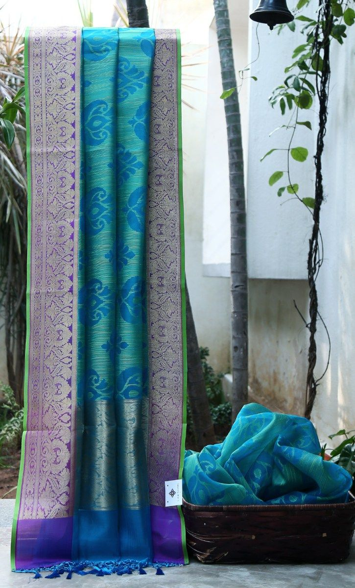 DODGER BLUE AND GREEN SOUTH KORA FLORAL BODY HAS ENIGMATIC WOVEN MAGENTA WITH GOLD ZARI BORDER AND PALLU WHICH GIVES THE SAREE SOPHISTICATED LOOK.