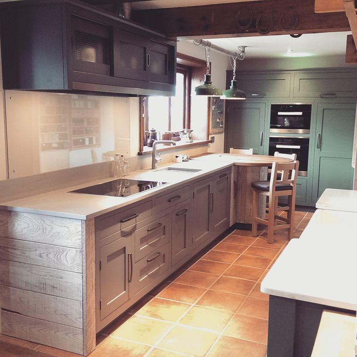 Hand Painted Grey (and green) Hallowed Furniture kitchen with an industrial edge; distressed end panel, quartz work top, stainless steel details, factory lights, wired glass and leather upholstered stools.