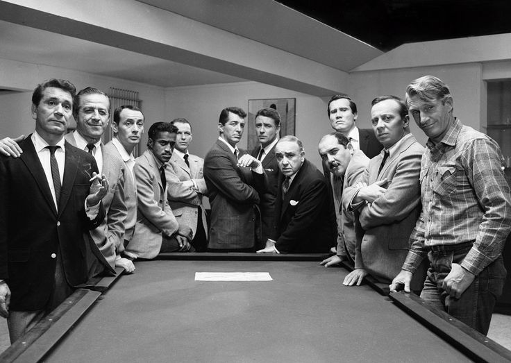 """Ocean's Eleven"" promo still, 1960.  L to R: Richard Conte, Buddy Lester, Joey Bishop, Sammy Davis Jr., Frank Sinatra, Dean Martin, Peter Lawford, Akim Tamiroff, Richard Benedict, Henry Silva, Norman Fell, Clem Harvey.  Plot:  Danny Ocean (Sinatra) and his former 82nd airborne pals decide to rob five Las Vegas casinos on New Year's Eve."