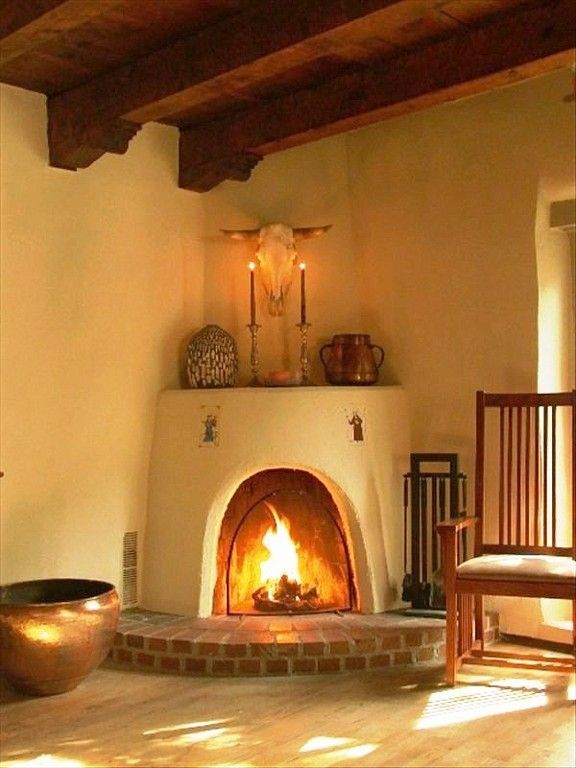 Southwestern style corner adobe fireplace with raised brick hearth