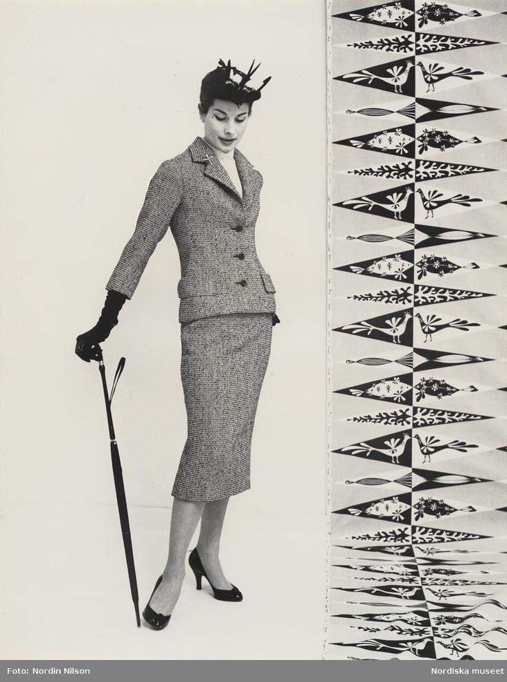 Original Dior, 1956. Modell i dräkt, coiffe, handskar och paraply i handen. Mönstrad textil vid sidan. Fotograf: Nordin Nilson. Modell: Erika Sundt.