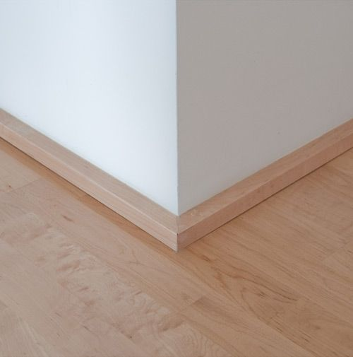 the low profile section covers the gap between the drywall and the floor and also provides a bumper for shoes, vacuum cleaners, etc. At hardwood applications we tend to match the base with the hardwood (in this case maple), at carpet applications we'll paint the base trim something close to the carpet. The end goal is to achieve a subtle profile that doesn't draw your attention to the base. The low profile of the 1×1 base often works much better with window systems