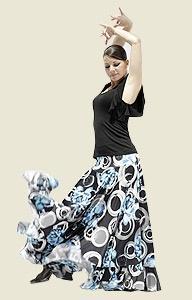 Falda para ensayo en tela estampada con motivos florales en tonos blanco, negro y turquesa con amplia capa y generoso vuelo. Está rematada con un volante. Diseño vistoso y práctico, ideal para la práctica del baile flamenco en clase o en el escenario.