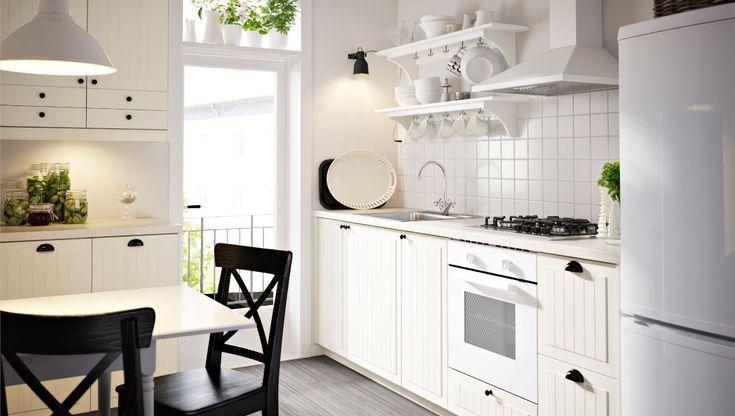 Køkken med hvide KROKTORP skuffefronter og låger og hvide skabe. hylderne
