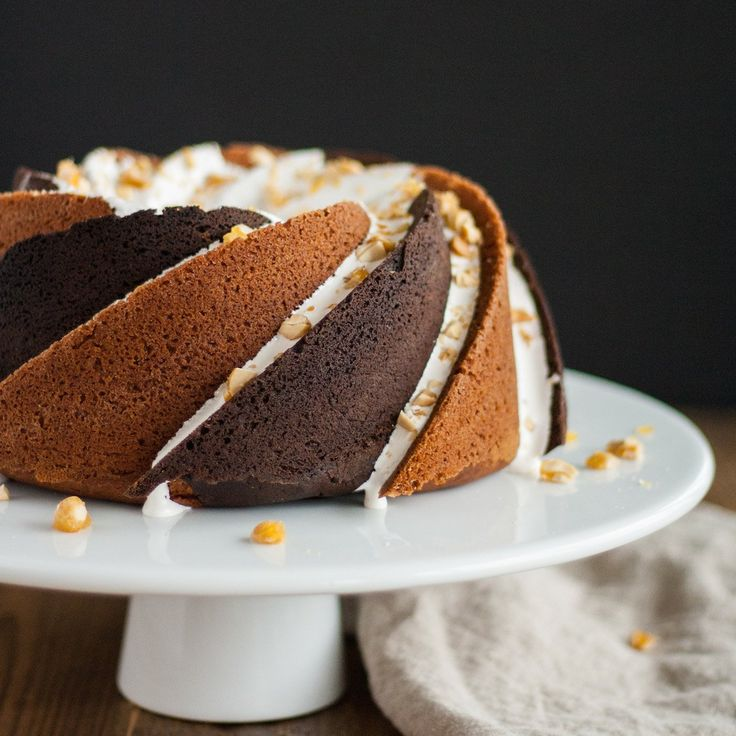 This Rocky Road bundt cake consists of alternating swirls of peanut butter and chocolate cake with a marshmallow glaze topped off with some candied peanuts.