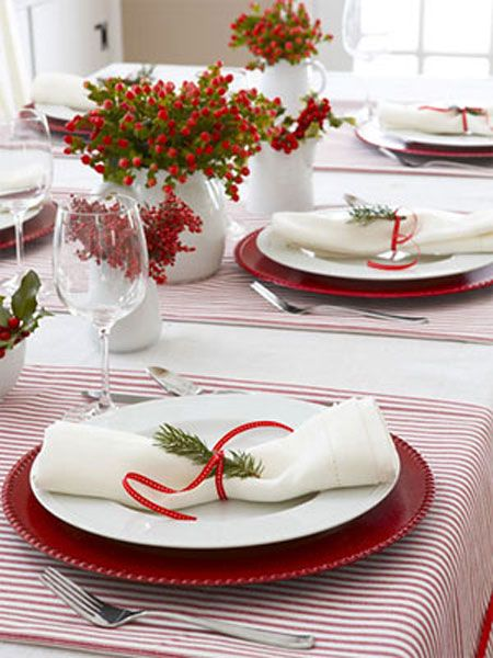 Christmas Table Ideas Using Red and White: Set the color scheme by topping a white linen table cloth with runners made out of red ticking fabric. Continue it with red chargers, ribbons and winter berries.