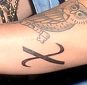 "Justin's ""X"" arm tattoo, which is actually a Greek symbol for ""Christ"" http://www.popstartats.com/justin-bieber-tattoos/"