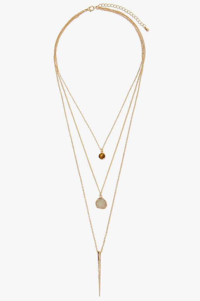 Oh hey, pretty thing. The Ojai Necklace features three delicate, layered gold chains with small brown crcle hems, clear crystal, and gold spike.