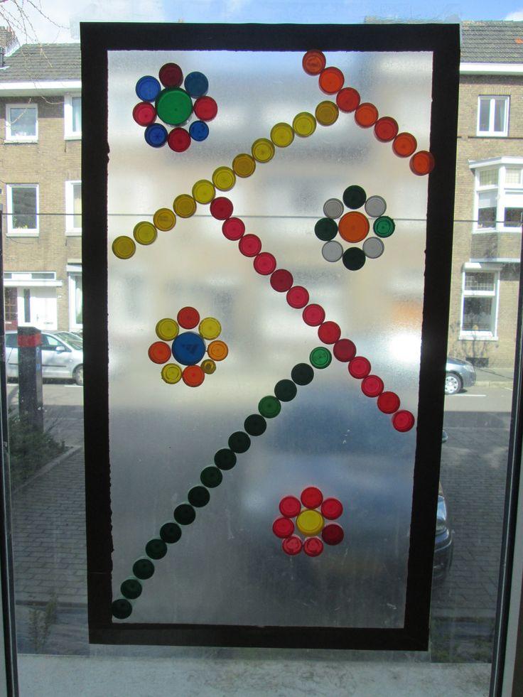 Plakplastic met tape op het raam plakken. En dan met doppen een kunstwerk er op maken. Je kunt de doppen er meerdere malen op en af doen, zodat je het plakplastic voor meerdere kunstwerken kunt gebruiken. Nutsschool Maastricht