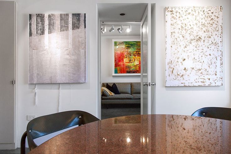 Works by Jessica Mein (left) and Analia Saban (right) flank the doorway leading into the living room, which displays the couple's prized Gerhard Richter painting.