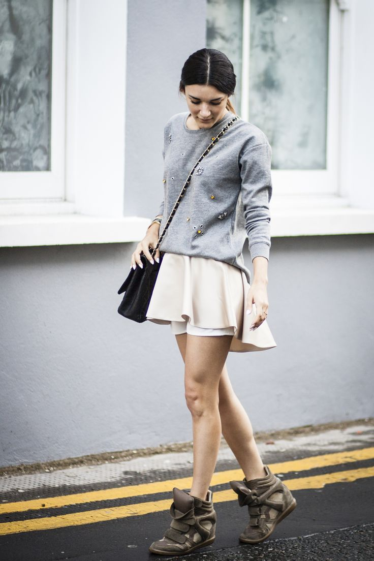 Anisa Sojka wearing grey embroidered Zara sweatshirt, cream Peggy Hartanto shorts, Chanel black caviar gold-chain cross-body bag, silver Fjord Timepieces Ingegerda watch and green Isabel Marant wedge sneakers. Street style shot in London by Cristiana Malcica.