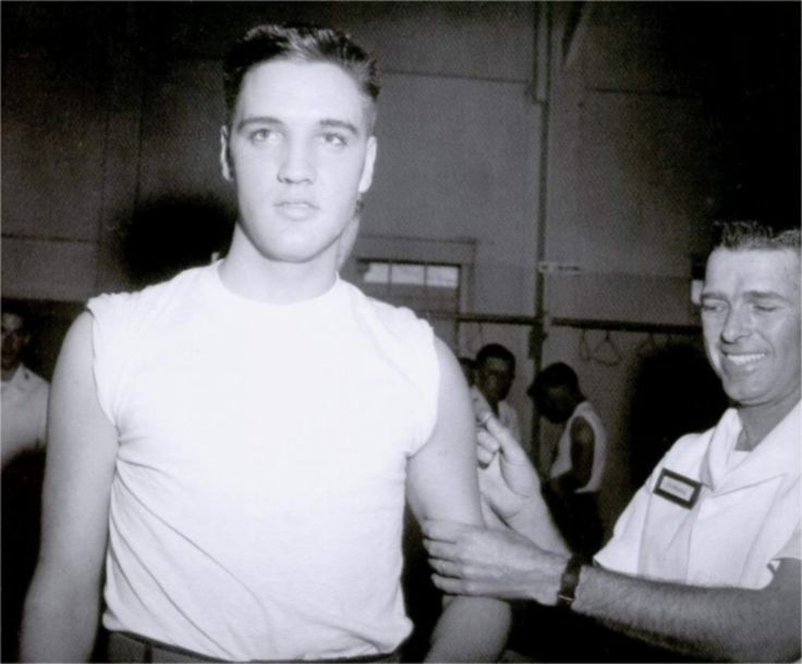 Private Presley is pictured getting a series of shots for typhoid, tetanus, and Asian flu by Sergeant Calvin Rhodes at Fort Chaffee, near Fort Smith, Arkansas on Wednesday, 26 March  1958, two days after his army induction.
