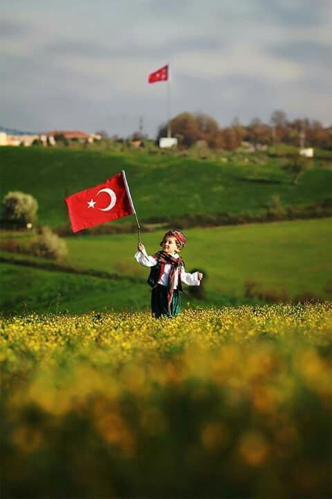 Lil Turk in traditional dress holding a Turkish flag in his hand.