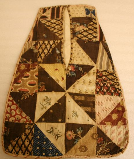 "Woman's pocket. The pocket is faced with large triangles of printed cottons and linens - one piece of blue resist, three pieces of white lined cotton embroidered with colored silks. The pocket is lined with blue and white checked linen and backed with bleached linen. Opening on front 9"" long. All edges bound. No tape remaining. ca. 1800. 17 1/2"" long x 12 1/2"" wide"