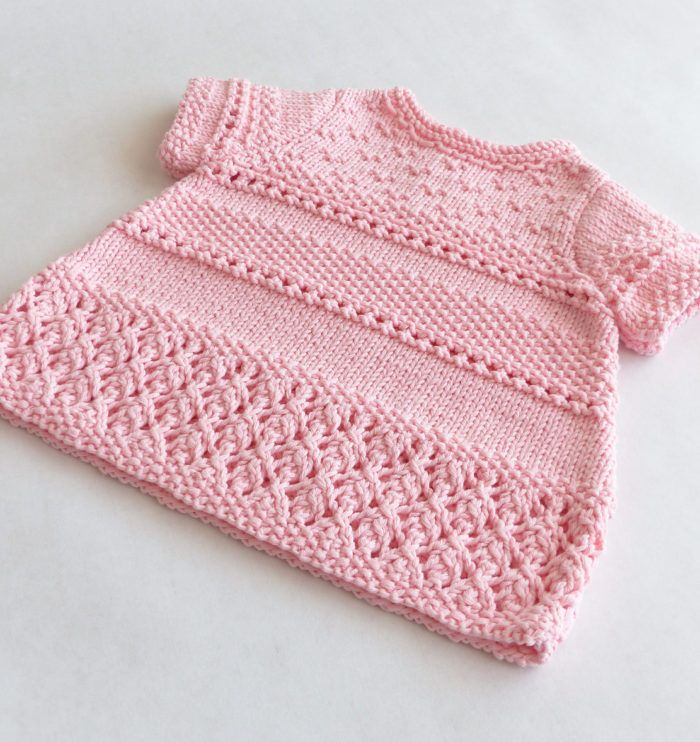Free Knitting Pattern for Ophelia Baby Dress - Baby dress with textured and lace stitches. Sizes 0-3 months (6 months, 9 – 12 months). Designed by Elena Canon. DK weight yarn. Available in English and French