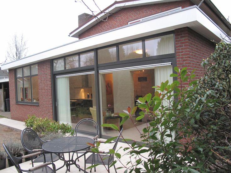 Groot raam aan achterzijde keuken die uitgeeft op tuin/terras