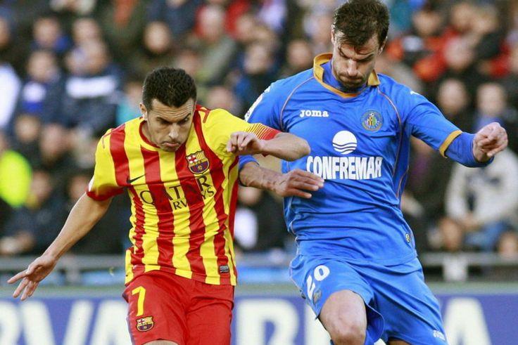 El delantero del Barcelona Pedro Rodríguez se dispone a marcar el primer gol de su equipo ante el defensa del Getafe Juan Valera