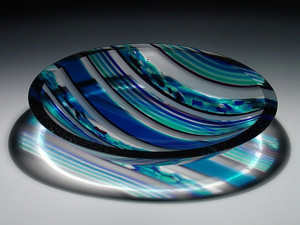 Blue. turquiose, and aqua striped vessel w/strong geometric elements. The embedded fluid-like inclusions are complemented by bold stripes of intense blue, turquoise, and aqua hues. A unique feature, the highly polished rim collects light & provides visibility inside the walls of the piece.