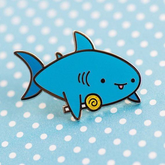 This little shark friend loves candy! And hes got a glittering lemon lollipop! This is a hard enamel pin and has a silver finish! Show off your shark and candy love with this pin!  The pin measures about 1.25 inch wide and comes packaged with a black rubber pin back.