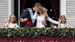 König Felipe VI. von Spanien (Mitte links) küsst Königin Letizia auf dem Balkon des Palastes, während Kronprinzessin Leonor (links) und Prinzessin Sofia dem Volk winken. © dpa - Bildfunk Fotograf: Juan Carlos Hidalgo