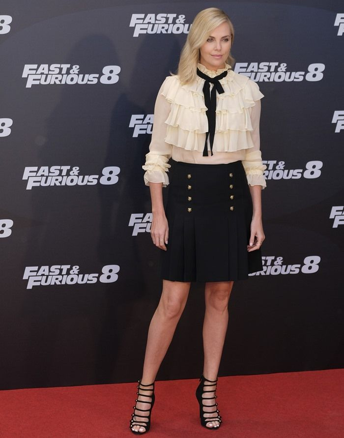 Charlize Theron in a Gucci skirt and blouse at the photo call for The Fate of the Furious at the Villamagna Hotel in Madrid, Spain, on April 6, 2017