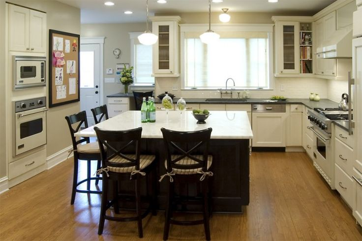 kitchen island with seating for 4 soapstone countertops hardwood floors glass front cabinets sink white backsplash chairs pendants ceiling lights traditional design of Fabulous Islands to See If You Want a Kitchen Island with Seating for 4