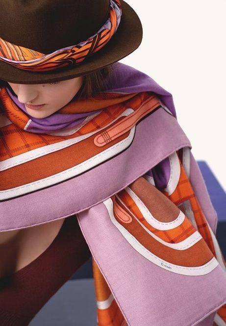 ピンク、オレンジ、ブラウンなど、エルメスらしい上品な色合いのストール。きっちりと揃えずに少しずらして巻いて、少しドレスダウンさせるテクニック。ウールハットに巻いたスカーフとの合わせ技がステキなコーディネート。