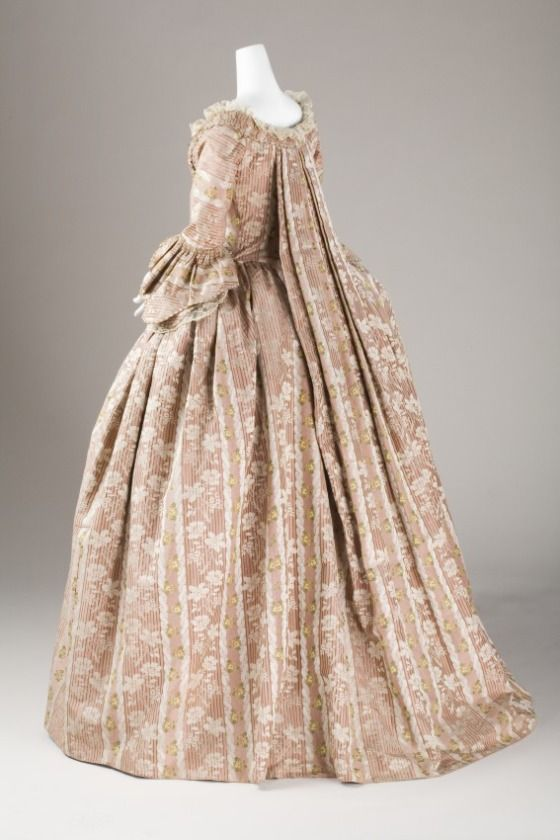 Back view, robe à la francaise (sack-back gown), France, 1760-1780. Striped salmon-coloured brocaded silk. A white leaf pattern is woven into the fabric and as well as floral sprays in various colours.