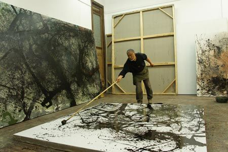 Hong Ling improvises on a painting in his workshop after he came back from a stroll in the mountains.